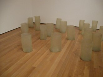 """Eva Hesse - Repetition 19, III, 1968, fiberglass and polyester resin, 19 units each 19 to 20 1/4"""" (48 to 51 cm) x 11 to 12 3/4"""" (27.8 to 32.2 cm) in diameter, Museum of Modern Art, New York"""