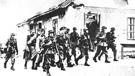 a black and white photograph of a group of a dozen German soldiers marching past a house with weapons slung over their shoulders