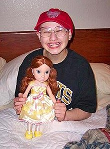 A young woman sitting upright in a bed, her legs under the blanket and the headboard and pillows behind her. She holds a large doll in front of her and is wearing a T-shirt, large glasses and a red baseball cap while smiling broadly