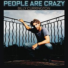 The cover has the artist wearing a blue t-shirt and jeans combination, crouching and having his right arm hold next to a black art deco fence. The song title is set above the image, colored in neon blue, with the artist's name below it in white.