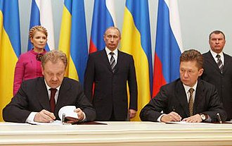 Russia–Ukraine gas disputes - Signing of the deal reached at the Moscow summit on 19 January 2009, by Oleh Dubyna and Alexei Miller (with Yulia Tymoshenko and Vladimir Putin standing in the background)