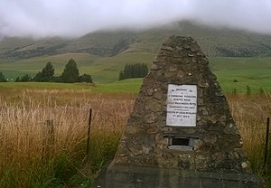 Eyre Creek (locality), New Zealand - Memorial cairn near the graveyard which is in front of the trees to the left..