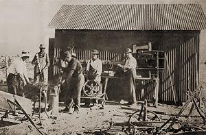 Llano del Rio - Colonists outside a crude machine shop at the Llano del Rio colony, 1914.
