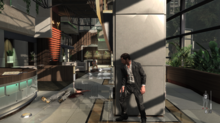 The player character positioned in cover behind a pillar, inside a building, while enemies hunt him down.