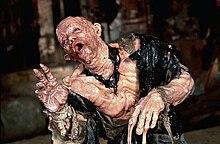 Закулисная фотография актера Пола Маккрейна в протезном костюме с изображением тающей кожи.