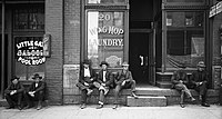 Men lounging outside saloon & Chinese laundry, Salt Lake City, 1910