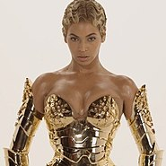 A woman wearing a golden metallic corset and a pair of sleeves of the same material, is standing and looking forward.
