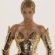 Eine Frau, die ein goldenes Metallkorsett und ein Paar Ärmel aus demselben Material trägt, steht und freut sich.