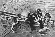Ten men in water, surrounding one man being floated on wooden poles and tires