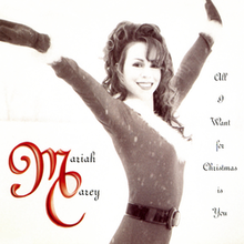 Carey wearing a Santa suit, while posing in an upright position. She has long brown curly hair, and is smiling. The background imagery is beige, with red letters that spell out the song's title.