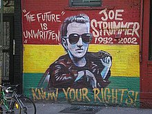 "A photograph of the painting of the memorial mural of Joe Strummer on the wall of the Niagara Bar in the East Village in New York City. The mural depicts Strummer (centre) surrounded by the words ""THE FUTURE IS UNWRITTEN"" (on the left), ""JOE STRUMMER 1952–2002"" (on the right), and ""KNOW YOUR RIGHTS!"" (bottom) on a horizontal tricolour of red, yellow, and green background"