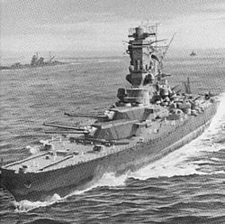 A large ship sails toward the reader, while four guns in two turrets point at about a 45-degree angle at something off in the distance
