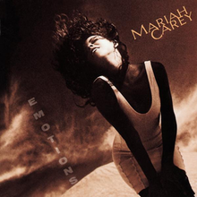 "A brunette woman in a white dress standing in front of a dark desert like background, the words ""MARIAH CAREY"" are on the left hand side of the artwork with the words ""EMOTIONS"" are towards the bottom right hand side of the artwork."