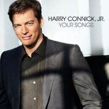 Harry Connick, Jr. in a black jacket and black shirt, white background, black text