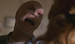 A mutant human with black eyes, sharp fangs, and no ears prepares to attack a woman.