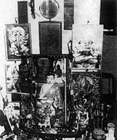 Various portraits and statuettes are arrayed on a small table and the wall it is against. A small round mirror hangs above this collection of religious items.