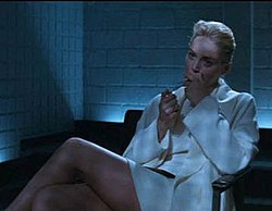 A blonde woman wearing a white jacket, top, and short skirt, her face half in shadow, sitting in an arm chair with her legs crossed. She holds a cigarette to her mouth with her right hand, and raises a lighter with her left. Behind her is dark furniture and the corner of the room, walled with white brick, from between the furniture and walls, unseen, floor-level lights cast a bluish glow over the scene.