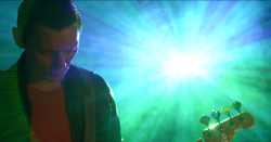 A screenshot from the music video; Richard Jones playing Bass, behind him is as an image projector creating a lens flare.
