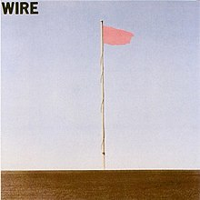 The album cover for the band Wire. The cover photo shows a single flagpole with a pink flag, against a blue sky.