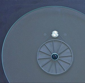 Belt-drive turntable - The functional relationship between the drive belt, sub-platter, and motor pulley, can be seen through the glass platter on a Rega Planar 3.