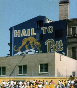 Hail to Pitt - Pennsylvania Hall, now demolished and replaced by a modern residence hall of the same name, from inside Pitt Stadium, also now demolished.  This side of Pennsylvania Hall shows the Hail to Pitt sign that existed in many variations throughout the years on the campus of the University of Pittsburgh. This version was painted for the 100th season of Pitt football in 1990. It depicts a stylized version of Giuseppe Moretti's Panther statues as well as the traditional script Pitt logo that served as the primary athletic logo from 1973 until 1997.
