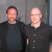 A photo of two men wearing black shirts standing outside a concrete building