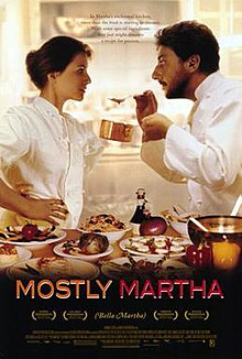 Mostly martha poster - man and women in chef's attire, looking intently at each other as man holds up small pan and spoon laden with food, leaning in to offer to woman