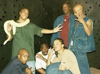 Outlawz - The group in 1996, on the set of the music video for Hit 'Em Up. Standing: Napoleon, E.D.I. Mean, and Hussein Fatal. Kastro, Makaveli The Don and Yaki Kadafi.