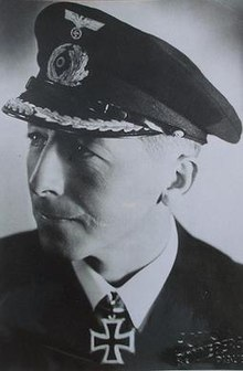 The head and shoulders of a man, shown in semi-profile. He wears a peaked cap, white shirt and a black jacket, and a military decoration in shape of an Iron Cross at his neck.