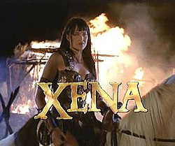 "A woman in leather armor sits on horse back with flames behind her. At the bottom of the screen in capital letters is the word ""Xena"" in gold lettering."