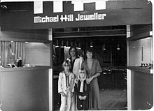 Michael Hill and family standing outside the entrance of their first jewellery store