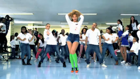 A woman that wears a white blouse, blue shorts, green socks, and red sneakers is standing. Behind her many people, similarly dressed, are dancing in the room.