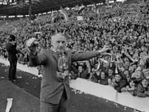 Bill Shankly - Bill Shankly during a lap of honour at Anfield in April 1973, wearing the scarf thrown to him by a Liverpool fan.