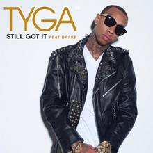 The cover consists of a white background that has the artist's name on the top left corner, boldly written in gold. Below it is the song title and featured artist's name, both colored in black and light gold respectively. The artist is centered on the cover, leaning his head towards his left, wearing a white shirt and black leather jacket covered in gold studs, sunglasses, and a gold watch and bracelet on his wrists.