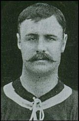 A black-and-white head-and-shoulders photograph of a man wearing a dark shirt with a light ring around the collar. He has short hair and a moustache.
