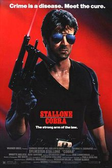 Against a red backdrop, Stallone dressed in black, holding a large gun, wearing sunglasses, and with a toothpick in his mouth.