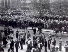 Several police officers on horses watch a large crowd standing in a public park.