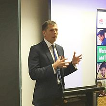 Michael Coutts-Trotter speaking at an event.jpg