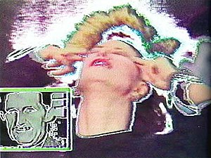 """Good Morning, Mr. Orwell - Pop singer Sapho performs """"TV Is Eating up Your Brain"""", with video effects. In the lower left is a still image of George Orwell."""