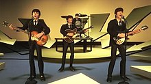 A virtual music set, composed of a small, round elevated stage and a further offset for the drum set, with several yellow-tinted arrow-like shapes mounted behind and in front of it, the arrows directed to the stage. The virtual Beatles are performing on this set.