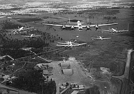 Head-on view of seven four-engined military aircraft flying over an airfield