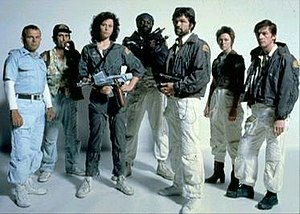 The seven principal cast members of Alien stand in front of a white backdrop, in costume and holding prop weapons from the film.