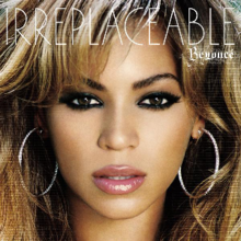 "A close-up image of a brunette woman who is looking forward. She wears soft make-up, which consists of black eyeliner, pink lipstick, and earrings. On the top, the words ""Beyoncé"" and ""Irreplaceable"" are written in white letters."