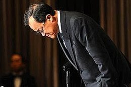 a bespectacled oriental man in a dark suit bowing with brown curtains as backdrop