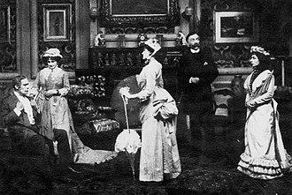cena do palco em trajes de 1885 com uma jovem se dirigindo a um pai severo