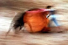 Blurred motion photo of bullfighter sweeping red cape over rushing bull.