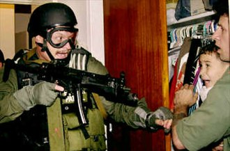 Elián González - Federal agent Jim Goldman (Assistant District Director, Investigations - Miami District INS) retrieves Elián from his relatives' home in Miami. This photo won the 2001 Pulitzer Prize for Breaking News.