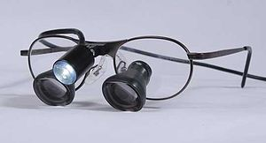 Loupe - A pair of dental loupes featuring in-lens magnification.  There is a loupe light mounted on the bridge of the loupes and side shields (not shown) on the temples to protect a dentist's eyes from splatter.
