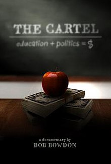 "Red apple on top of stack of money on desk in front of a classroom blackboard.  Blackboard reads ""education + politics = $"""