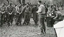 A chaplain reads from a bible while a formation of men stand in the background with heads bowed.